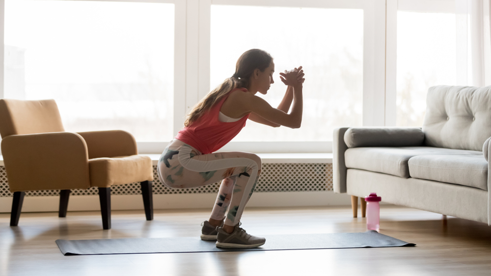 woman doing squat morning exercise alone in living room